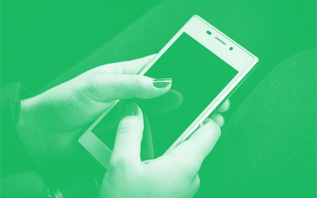 Photo of person using smartphone with a green overlay.