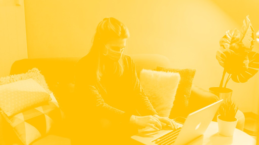 Woman sat at a table, using a laptop and wearing a face mask